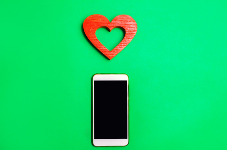 dependence on social networks. phone smartphone and heart on a green background. online dating, flirting, message and calling your loved one. concept of love and communication