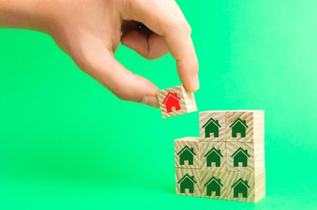 the businessman's hand and wooden cubes with houses. investment in real estate. buildin, sale, rent, purchase of a house. affordable housing. plan for moving houses 写真素材