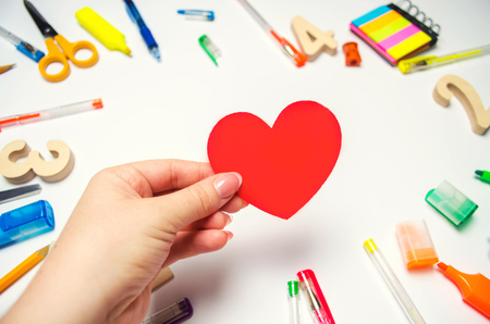 I Love School! the student holds the heart in his hands on the background of the desk. love of learning. stationery. back to school. education. teenage first school love. Stock Photo - 105154451