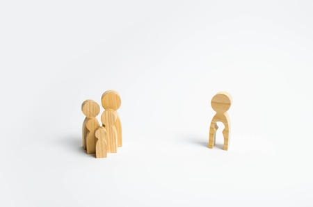 Wooden figurines of people in the shape of a family and a man with the emptiness of a child inside the body on a white background. The concept of family planning, treatment of infertility.