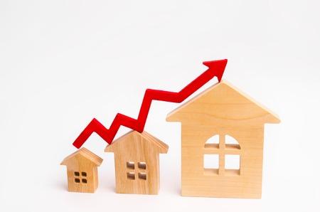Le case di legno stanno in fila da piccole a grandi con una freccia rossa verso l'alto. concetto di forte domanda di immobili. aumentare l'efficienza energetica degli alloggi. aumento dei prezzi delle case. proprietà. Archivio Fotografico - 105725321