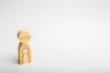 a wooden figure of a pregnant woman. the future mother is waiting for the baby. expectation and birth of a child. the last months of pregnancy. minimalism. copy space
