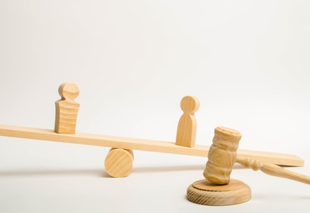 Two people on the scales and a judge hammer on a white background. The concept of litigation. The plaintiff and the defendant. Dispute resolution, administrative and criminal liability.