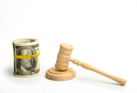 A wooden judge hammer and a bundled bundle of dollars on a white background. Franklin's eyes on the banknote are covered with an elastic band. The concept of corruption in the judicial sphere.