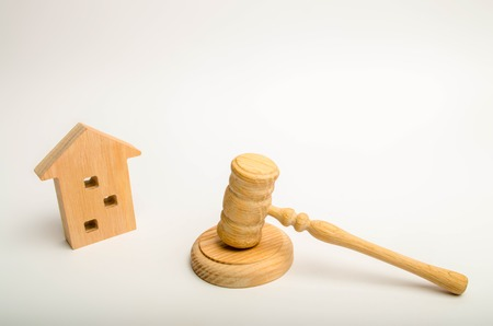 Wooden apartment house and hammer of the judge on a white background. The concept of the trial of an apartment building, the examination of cases between the tenants of the house.