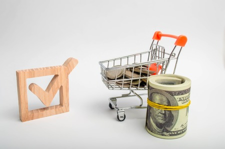 Wooden checkbox and a cart with coins. Attracting resources and resources to solve problems. Investment climate. Legislative protection of investors interests. Corruption in elections. Lobbying.
