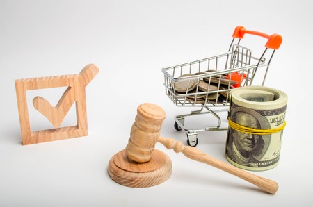 A wooden checkbox and a trolley with coins and a hammer of the judge. Lobbying of interests of investors and business groups, political company. Corruption in government, the judiciary and elections.