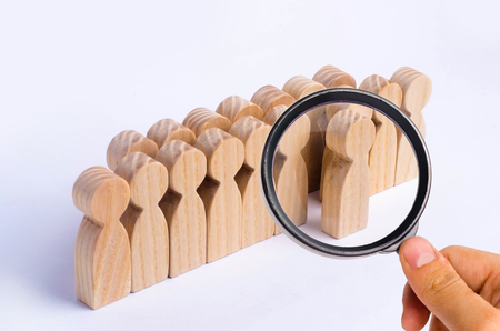 The chosen person among others. A human figure of stands out from the crowd. Wooden figures of people. A talented worker, a successful choice. Promotion. Concept of search for a worker.