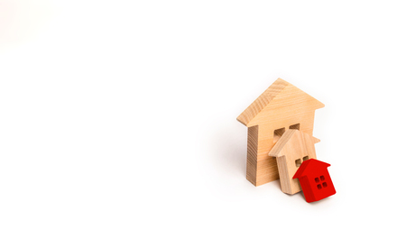 Small wooden houses fall on the big house as a domino. The concept of buying real estate. Insurance and investment risk. Falling prices in the real estate market. Growth in demand. Catastrophe. 免版税图像 - 106365448