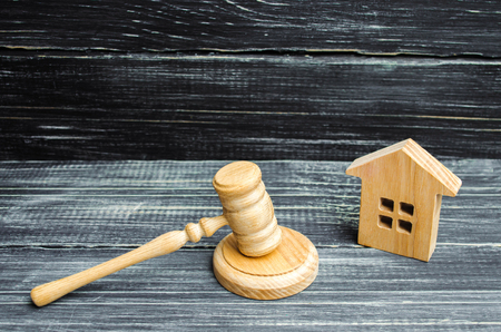 wooden house and a hammer of the judge on a black background. Court cases on property and real estate. Confiscation and nationalization, real estate scam. Issuance of permits for construction. court