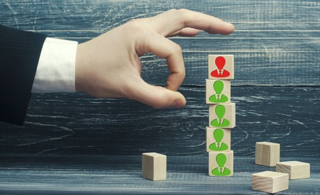 the businessman removes / dismisses the employee from the team. management within the team. wooden blocks with a picture of workers. control arm. leader Stock Photo