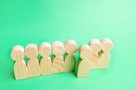 a man comes out of the crowd. individual opinion. Concept of search for worker. talented worker. personnel search. divergent views. school line. wooden figures of people