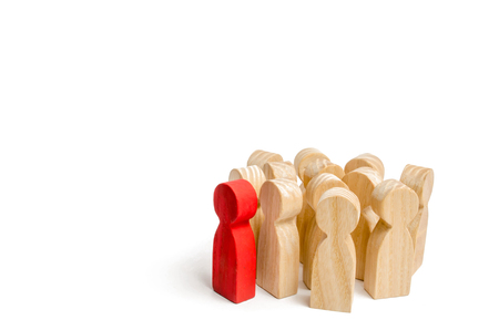 Group of wooden people figurines. Red man stands out from group, Crowd, meeting, social activity. Society, social group. Herd instinct, management of people. Human resources, workers stand together.