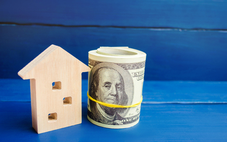 wooden house and dollars on a blue background. concept of real estate. buying, selling, renting. credit for property. sale apartment. mortgage. affordable housing for a young family. loan