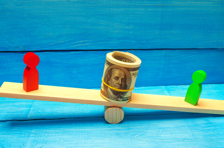 wooden figures of people on scales and dollars between them. a dispute between two businessmen. trial. debt restructuring. wage arrears. protection of employee rights. court. Labor Law Stock Photo