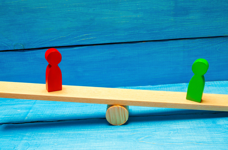 wooden figures of people. rivals in business stand on the scales. trial. conflict. victory and defeat. bad and good worker. the red figure outweighs the green one. competition. success and failure