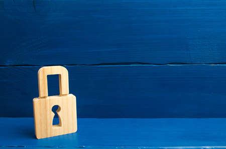 a wooden padlock on a blue background, information, entrance. concept of the preservation of secrets, information and values. Protection of data and personal information. Hacking attack, hacking