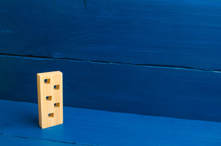 Apartments and apartments. Minimalism. for presentations. Wooden figure of a multi-storey house on a blue background. Three-story house. Buying and selling of real estate, construction.