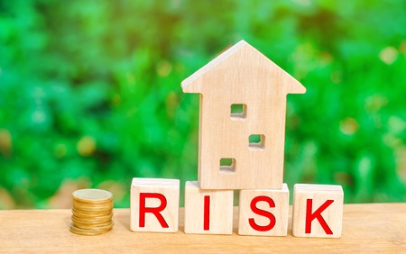 wooden house and cubes with the word risk. The concept of risk, loss of real estate. Property insurance. Loans secured by home, apartment. Financial risks, litigation. Stock fotó