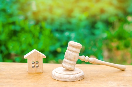 A miniature wooden house and a hammer of the judge. Auction to buy  sell a house. Forced eviction and confiscation. Clarification of ownership of property. Concept settlement of litigation. Court 写真素材