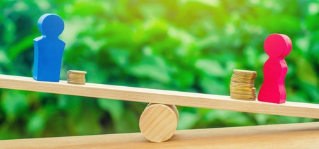 wooden figures of a man and a woman stand on the scales and coins between them. concept of the gender pay gap. Income inequality. oppression of women. gender discrimination. balance Stock Photo