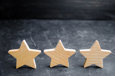 three wooden stars on a black background. The concept of the rating of hotels and restaurants, the evaluation of critics and visitors. Quality level, good service. selective focus Banque d'images