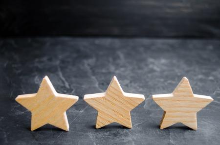 tres estrellas de madera sobre un fondo negro. El concepto de rating de hoteles y restaurantes, la valoración de críticos y visitantes. Nivel de calidad, buen servicio. enfoque selectivo Foto de archivo