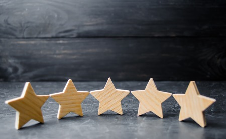 Five wooden stars. Get the fifth star. The concept of the rating of hotels and restaurants, the evaluation of critics and visitors. Quality level, good service. selective focus Archivio Fotografico