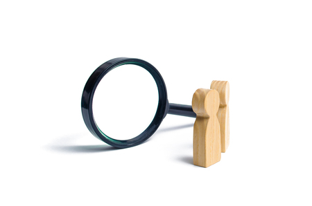 Two wooden human figure stands near a magnifying glass on a white background. The concept of the search for people and workers. Search for vacancies and work. Human resources, management.