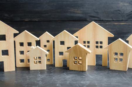 Hölzerne Stadt und Häuser. Konzept steigender Preise für Wohnung oder Miete. Wachsende Nachfrage nach Wohnraum und Immobilien. Das Wachstum der Stadt und ihrer Bevölkerung. Investitionen. Agglomeration und Urbanisierung