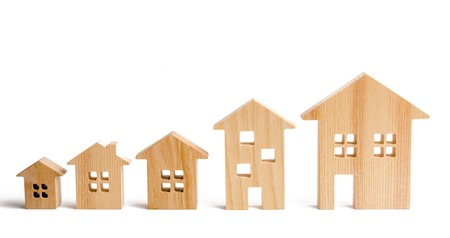 Wooden houses stand in ascending order on a white background. Isolate The concept of increasing population density and high-rise buildings. Agglomeration and urban growth. Selective focus 写真素材