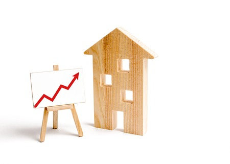 Wooden houses and stand with red arrow up. Growing demand for housing and real estate. The growth of the city and its population. Investments. concept of rising prices for housing or rent.
