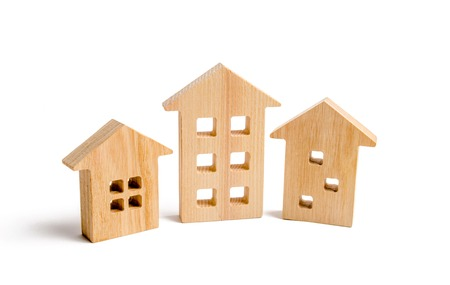 Wooden houses on a white background. Growing demand for housing and real estate. The growth of the city and its population. Investments. The concept of rising prices for housing Selective focus