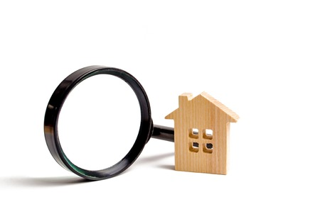 Wooden house and magnifying glass on a white background. Buying and selling real estate, building new buildings, offices and homes. House search. The concept of urban planning, infrastructure projects
