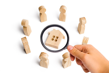 Wooden figurines of people stand around the house. Search for a new home and real estate. Buying or selling a home. Moving to a new home. Rent or construction. Buying a property. Investments 版權商用圖片