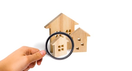 Magnifying glass is looking at the City of wooden houses on a white background. The concept of urban planning, infrastructure projects. Buying and selling real estate, building new buildings.