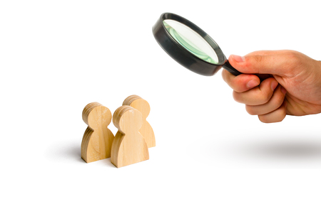 Magnifying glass is looking at the Three people stand together and talk. Three wooden figures of people conduct a conversation on a blue background. Communication, meeting place. Selective focus