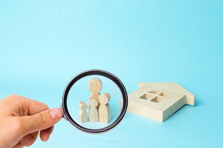 Magnifying glass is looking at thefamily stands near the ruined fallen house. Loss of housing, home insurance. Accident, war. Buying immobility Homeless family. People stand near the house