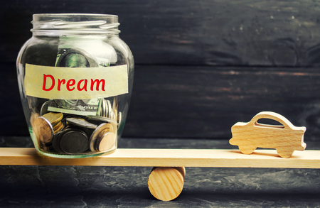 Wooden model of the car and a glass jar with coins and the inscription