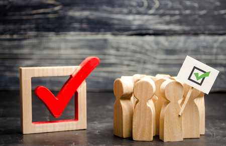 A group of people stand near the tick in the box. Voters and the political process. Political movement, faction, party. Agitation and propoganda, referendum, poll. Voting in election. Selective focus