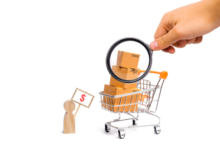 Magnifying glass is looking at a man with a poster sells goods. concept of commerce and trade, the sale and purchase of products, shopping on the Internet, deliverySupermarket cart with boxes goods Stockfoto