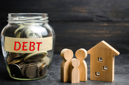 Glass jar with coins and the inscription  Debt , family and wooden house. Real estate, home savings, loans market concept. Payment of real estate tax. Mortgage. Risks of buying a house. Foreclosure