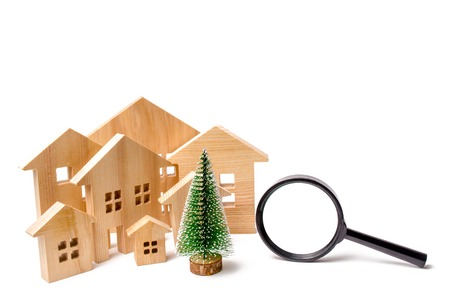 Wooden houses and Christmas tree and magnifying glass. The concept of search a hotel or a resort for the New Year's holiday and recreation. Holiday discounts. Christmas Sale of Real Estate. Discounts