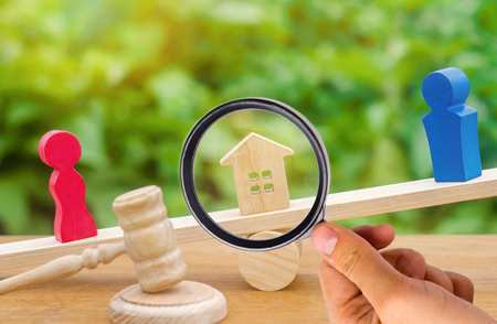 division of property by legal means. clarification of ownership of the house. wooden figures of people. man and woman are standing on the scales. trial, conflict. court. divorce