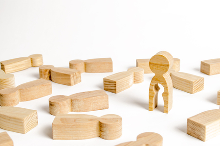 A wooden figure of a man with an empty child-shaped inside the body is standing among other people. The concept of missing a child searching for a baby. Childlessness, sterility in women Stockfoto