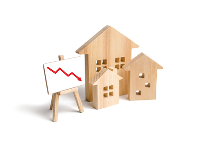 Figures Wooden houses and red arrow down. The concept of falling prices and demand for real estate, crisis and recession, the fall in the rate of construction of new housing and buildings. Low quality Foto de archivo