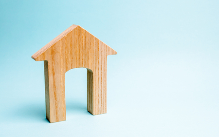 Wooden house on a blue background. Lending to the public. The concept of affordable housing and mortgages to buy a house. Buying and selling apartments and property, real estate.
