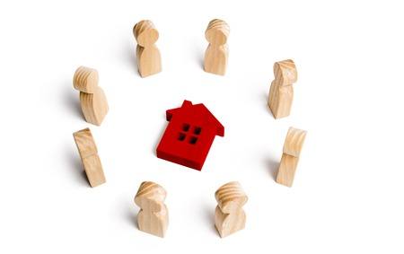 Wooden figurines of people stand around the house. Search for a new home and real estate. Buying or selling a home. Moving to a new home. Rent or construction. Buying a property. Investments Stock Photo