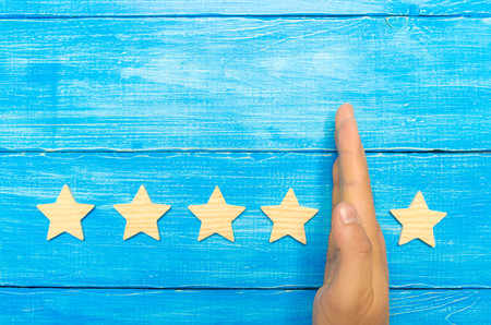 hand of the businessman separates the fifth star from the other four. loss of the fifth star, the fall in rating and recognition. critic takes the fifth star from a hotel, restaurant. selective focus Banco de Imagens
