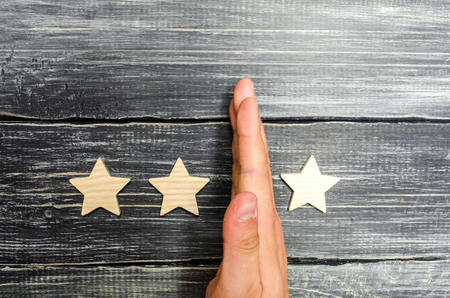 hand of the businessman separates the third star from the other four. loss of the third star, the fall in rating and recognition. critic takes the third star from a hotel, restaurant. selective focus